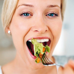 Frau mit einer Gabel im Mund